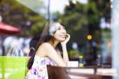 Smiling young woman thinking in cafe shop — Stock Photo