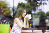 Smiling young woman drinking coffee in cafe shop — Stock Photo