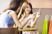 Happy young woman looking at phone in coffee shop — Stock Photo