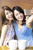 Happy girlfriends taking a selfie in coffee shop — Stock Photo