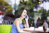 Smiling young woman talking on the phone in cafe shop — Stock Photo