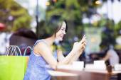 Smiling young woman looking at smart phone in cafe shop — Stock Photo