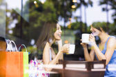 Two young woman chatting in a coffee shop — Stock Photo
