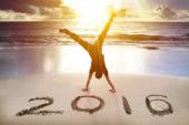 Happy new year 2016. young man handstand on the beach — Stock Photo