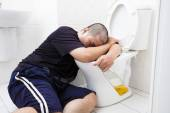 Drunk fat man with wine bottle in toilet — Stock Photo