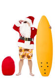 Happy Santa Claus standing with surf board — Stock Photo
