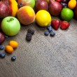 Border of mixed fruits with water drops on wooden texture — Stock Photo #51887803