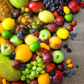 Mix of  Organic Fruits  with water drops on dark wooden table — Stock Photo