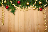 Christmas background with firtree, baubles and ribbons on wood — Stock Photo