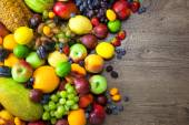 Mix of Fresh Fruits  with water drops on dark wooden table — Stock Photo