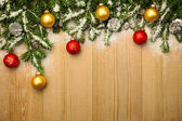 Christmas background with firtree and baubles on wood with snow — Stock Photo