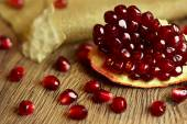 Raw pomegranate with seeds on wood — Stock Photo
