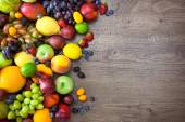 Different Organic Fruits  with  water drops on wooden table back — Stock Photo