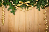 Christmas background with firtree, bow and ribbons on wood — Stock Photo