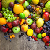 Organic Fruits  with water drops on dark wooden table — Stock Photo