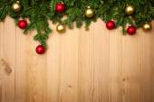 Christmas background with firtree and baubles on wood — Stock Photo