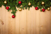 Christmas background with firtree and baubles on wood — Photo