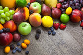 Mixed fresh Fruits on the  wooden background  with water drops — Stockfoto