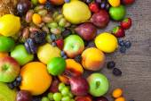 Mix of Colorful Fruits  with water drops on wooden background — Stock Photo