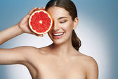 Smiling girl with grapefruit, natural organic raw fresh food concept — Stock Photo
