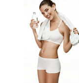 Seductive healthy woman with training body holds water and towel — Stock Photo