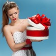 Thoughtful girl holding holiday or birthday presents, gift box on blue background. Holidays, celebration, birthday concept — Stock Photo #65903911