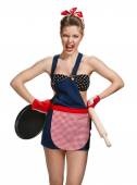 Quarrelsome maid wearing apron with wooden rolling pin and black frying pan — Stock Photo