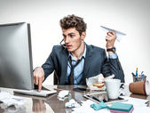 Office worker with paper plane in his hand typing — Stock Photo