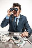 Young businessman looking through binoculars — Stock Photo