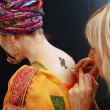 Process of drawing henna applying on the back — Stock Photo #59105587