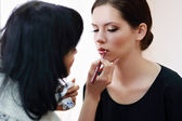 Woman applying make-up by make-up artist — Stock Photo