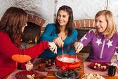 Friends having fondue dinner — Stock fotografie