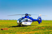 Police helicopter on a green grass field preparing to take off — Stock Photo