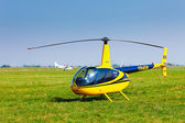 Helicopter on a green grass field preparing to take off — Stock Photo