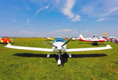 White airplane on a green grass field — Stock Photo