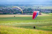 Paragliders flying over green fields — Stock Photo