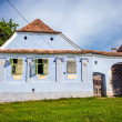 Blue painted traditional house with green shutters from Viscri v — Stock Photo #73895795