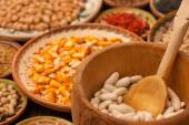 Various grain beans in small clay plates on natural textured woo — Stock Photo