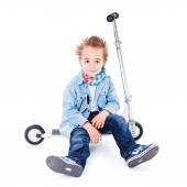 Tired small boy resting on scooter — Stock Photo
