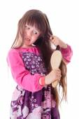 Little girl combing her frizzy hair — Stock Photo