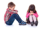 Angry sulking children sitting on the floor — Stock Photo