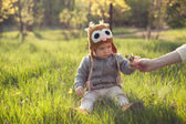 Cute baby in knitwears playing at the garden — Stock Photo