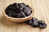 Prunes in wicker bowl  — Stock Photo
