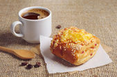 Bun with cheese and coffee cup — Stock Photo