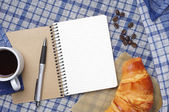 Notepad, croissant and coffee — Stock Photo