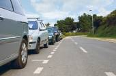 Cars parked on the side of an empty road — Stockfoto