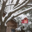 Red barn birdhouse on tree in winter — Stock Photo #57692665