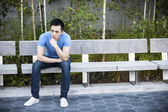 Serious young asian man on bench — Stock Photo