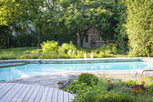 Garden and swimming pool in backyard — Stock Photo