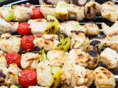 Barbecuing chicken, vegetables on spear over charcoal grill — Stock Photo